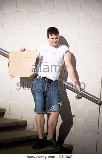Jobless Disadvantaged Poor Person Standing On The Broke Streets Of Unemployment Holding Up A Blank Sign Of Poverty - Stock Image