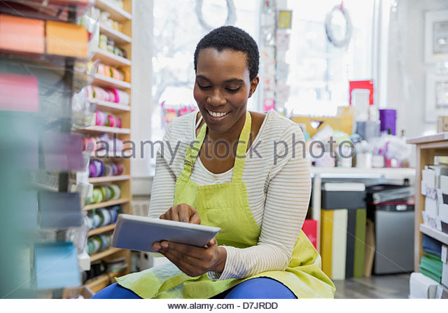 Female small business owner taking inventory with digital tablet - Stock Image
