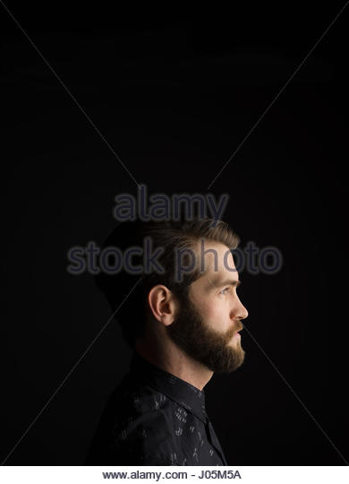 Profile portrait serious brunette man with beard looking away against black background - Stock Image