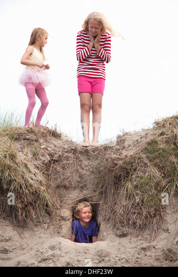 Boy hiding in hole in dunes with girls above, Wales, UK - Stock Image