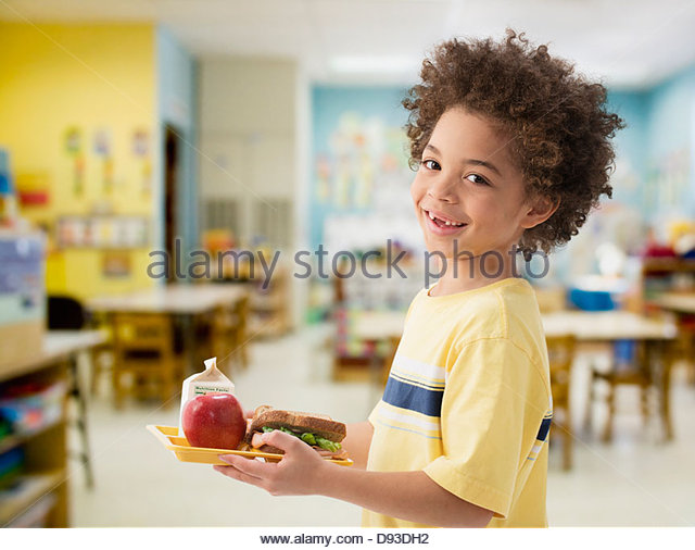 Mixed race boy having lunch at school - Stock Image