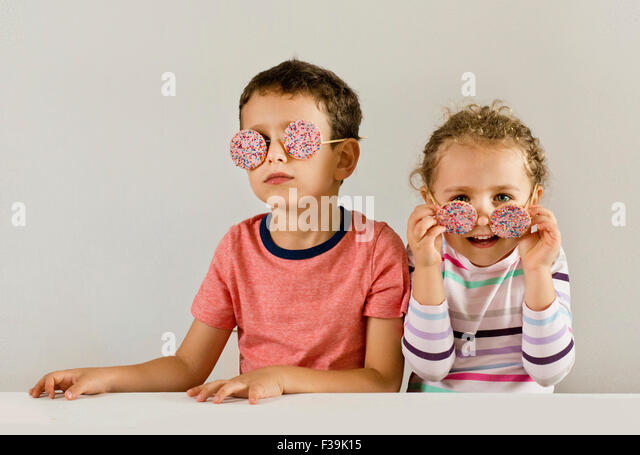 Boy and girl wearing sunglasses made of cookies covered in sprinkles - Stock Image