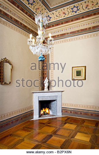 Vignette of Italian fireplace in corner with chandelier and decorated ceiling - Stock Image