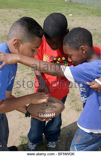 Miami Florida Moore Park touch football huddle sport game strategy Hispanic Black boy boys child student playground - Stock Image