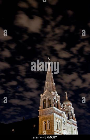 Night shot of a Catholic church with eerie sky. - Stock-Bilder