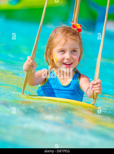 Closeup on cheerful baby girl with face paint swinging on water attractions, having fun in poolside, summer vacation - Stock-Bilder