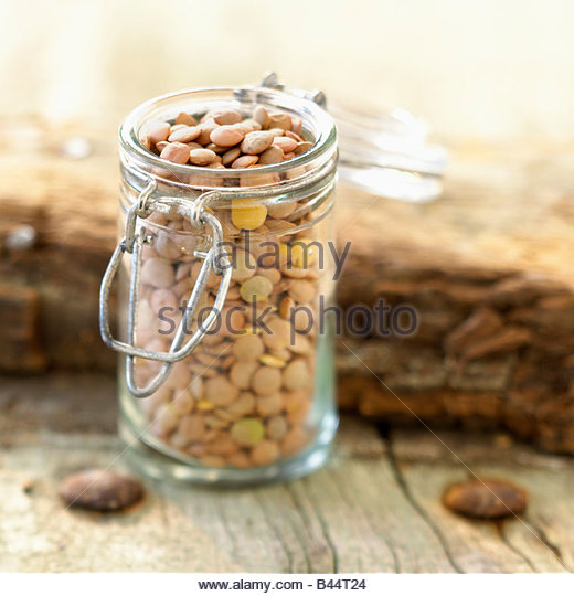 Small glass jar of pink lentils - Stock Image
