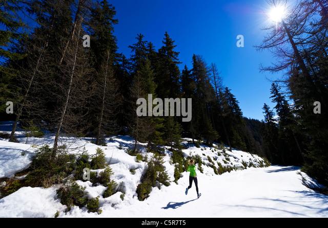 A woman jogging through a snowy mountain forest. - Stock-Bilder