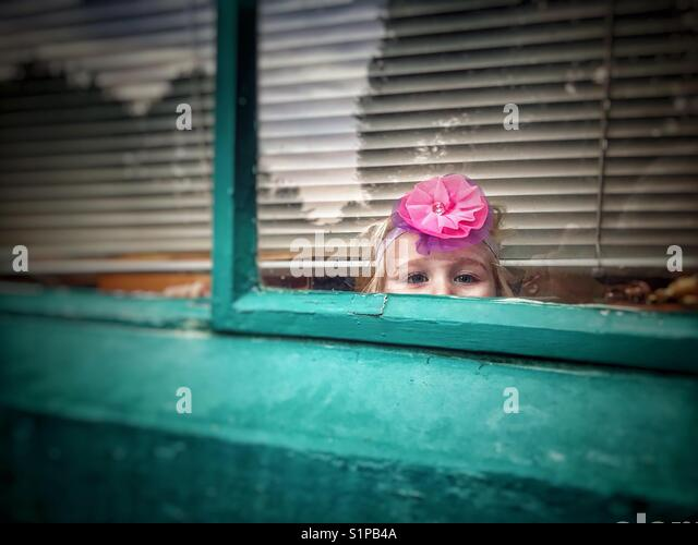 Small girl peeking out from a window - Stock Image