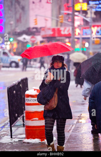 Snowing on a woman in Times Square, New York City - Stock Image