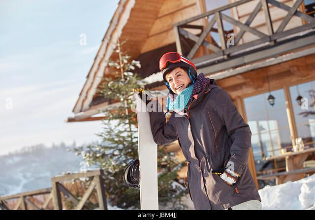 Smiling female snowboarder with snowboard outside sunny cabin - Stock-Bilder