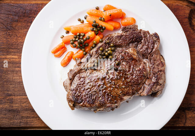 Grilled Beef steak with carrot and green pepper on white plate - Stock Image