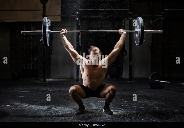 Bare chested young man weightlifting barbell in dark gym - Stock Image