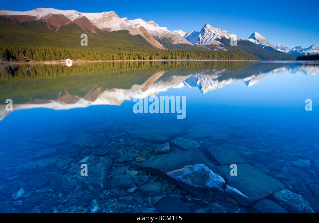 Crystal clear water with reflections at Maligne Lake Canadian Rockies Jasper National Park Alberta Canada October - Stock Image