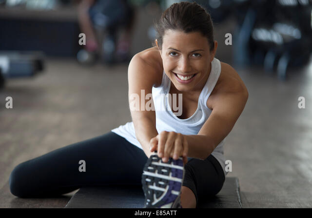 Woman at gym warming up with leg stretches - Stock Image