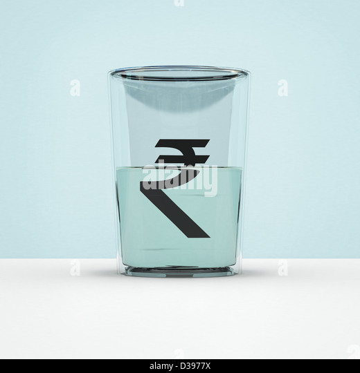 Glass half full with rupee symbol representing hope of currency growth - Stock Image