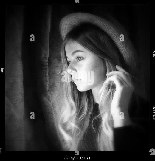 Teenage girl looking out of a window - Stock-Bilder