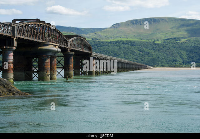 The famous railway bridge crossing the Estuary of the Afon Mawddach (River Mawddach) at Barmouth in Wales - Stock Image