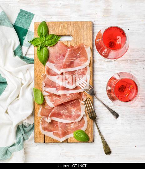 Prosciutto di Parma ham slices and rose wine glasses - Stock Image