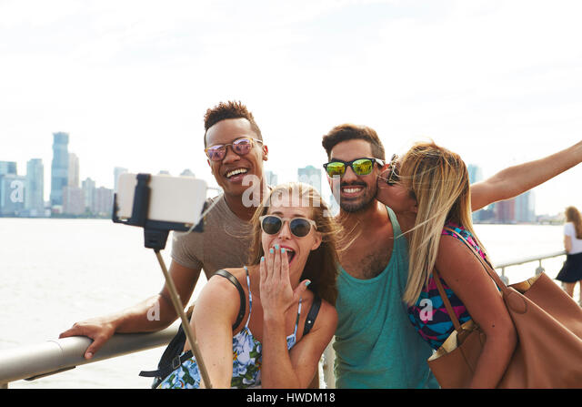 Four adult friends posing for smartphone selfie on waterfront with skyline, New York, USA - Stock-Bilder