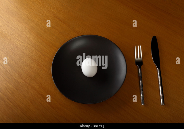 Organic Egg on Black Dinner Plate - Stock Image