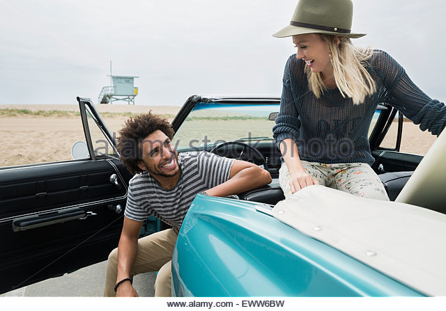 Young couple in convertible arriving at beach - Stock Image