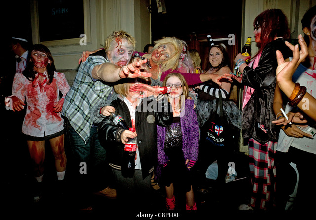 A family of Zombies posing outside a pub during a Zombie Walk and pub crawl for Halloween Piccadilly Circus London - Stock Image