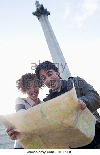 Happy couple with map below monument - Stock Image