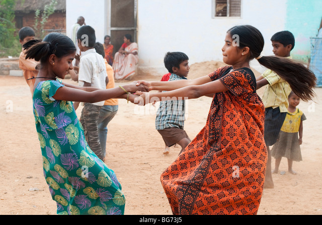 Indian girls swinging around in their village. Nallaguttapalli, Andhra Pradesh, India - Stock Image