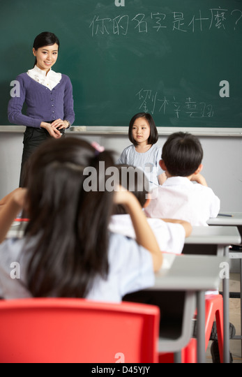 Pupil And Teacher Standing By Blackboard In Chinese School Classroom - Stock Image