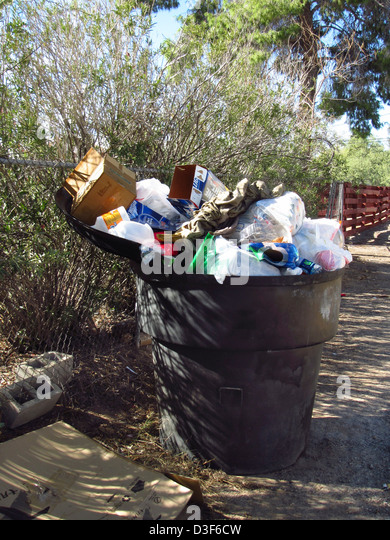 Residential garbage dumpster overflowing with trash - Stock Image