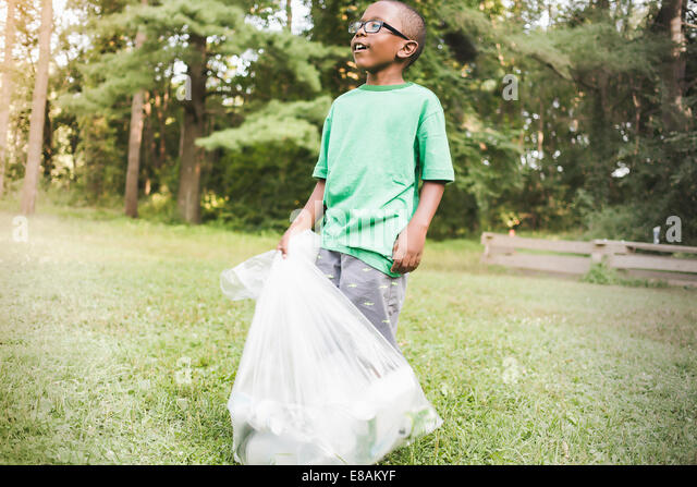 Boy with bag of picked up rubbish in parkland eco camp - Stock Image