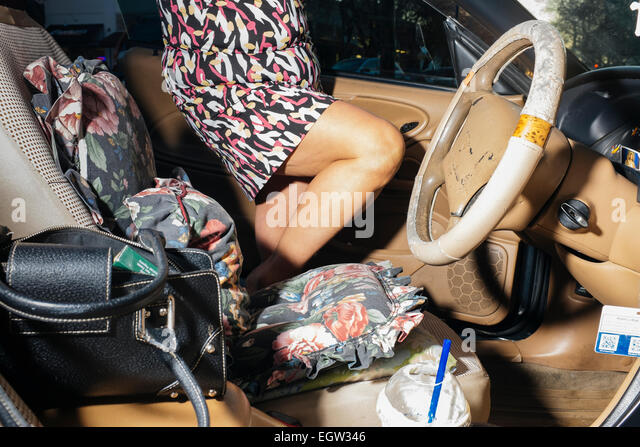 Mid section of woman getting into her car. - Stock Image