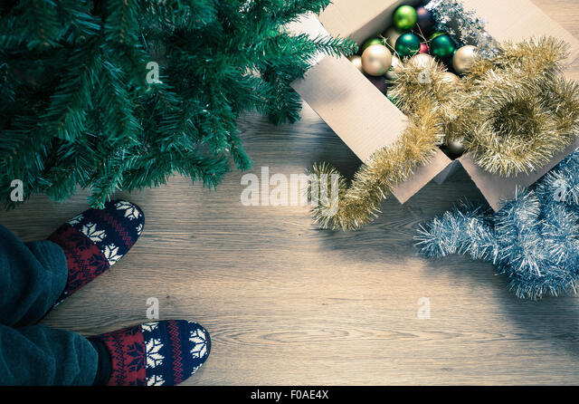 Person wearing slippers with christmas decorations, high angle - Stock Image