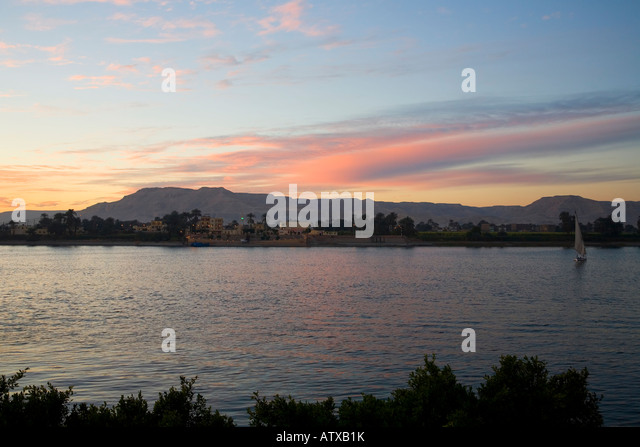 River Nile at dawn from Luxor east bank looking to Theban Mountains and Valley of the Kings Egypt North Africa - Stock Image