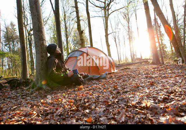 Man drinking coffee by tent in forest - Stock Image