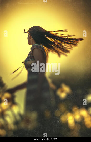 happy young woman dancing in summer meadow with yellow flowers - Stock-Bilder