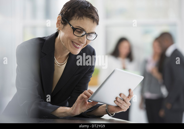 An office interior A woman in a black jacket using a digital tablet - Stock Image