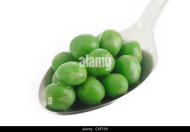 cooked green peas in spoon - Stock Image