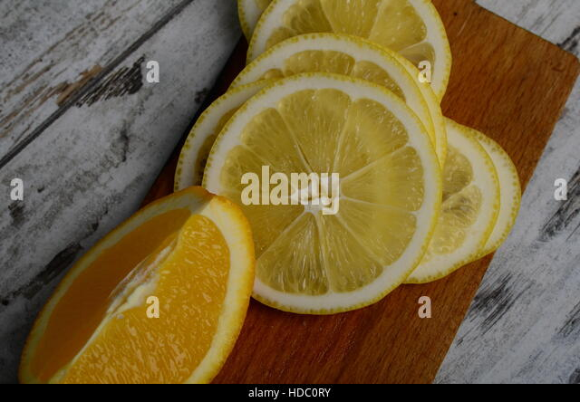 lemon, lime and tangerine on wooden cutting board - Stock Image