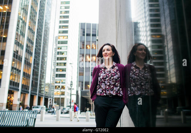 Low angle view of smiling businesswoman standing by glass window in city - Stock-Bilder