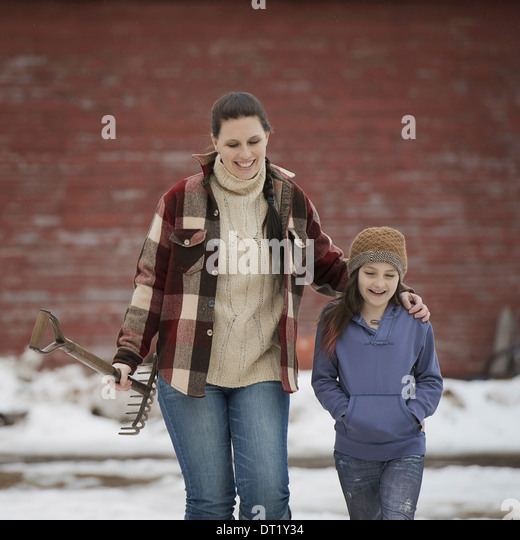 A woman and a young girl walking across a snow-covered farmyard - Stock Image