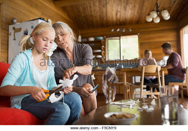 Grandmother and granddaughter cutting paper chain in cabin - Stock Image