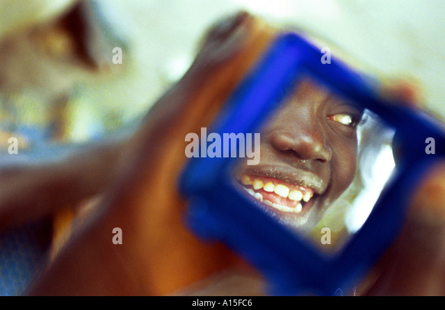 Khady Balde looks at herself at one of the few mirrors that exist in the Fulani village of Dembel Jumpora in teh - Stock Image