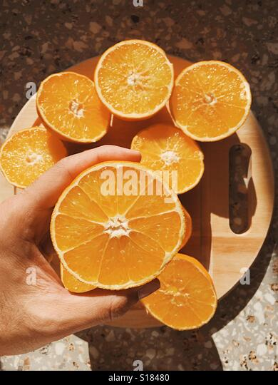 A hand holds a half sliced orange ready to be squeezed for a fresh morning juice on a sunny day. Seen from above. - Stock-Bilder