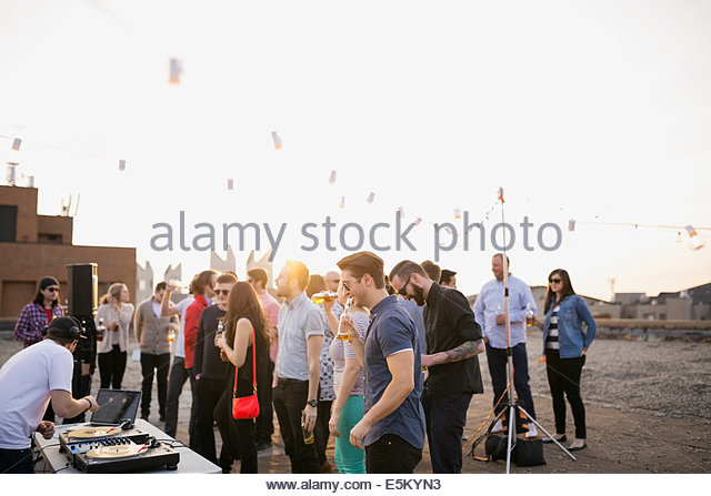 DJ and crowd at urban rooftop party - Stock Image