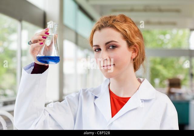 Chemist holding a blue liquid - Stock Image