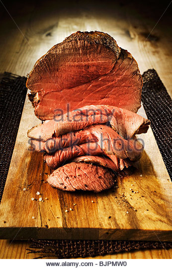 Roast beef, slices carved, on chopping board - Stock Image