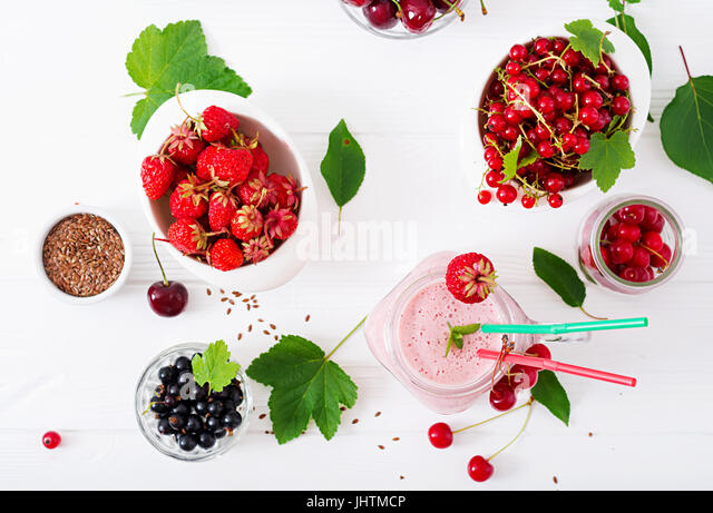 Yoghurt-strawberry smoothies in a jar on a white background. Flat lay. Top view - Stock Image