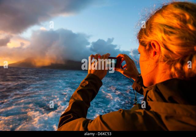 Tourist photographing Tau Island at sunrise, Manua Island group, American Samoa, South Pacific, Pacific - Stock Image